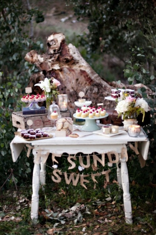 a vintage white table with a gold letter garland, neutral blooms and crates and suitcases as sweets stands