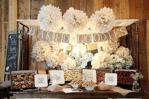a vintage rustic dessert table with a burlap garland, white paper flowers, sweets in crates, baby's breath in jars