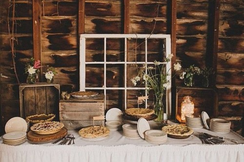 a rustic vintage dessert table with crates as sweets stands, a window, a jar with lights and some blooms in a vase is a cool idea