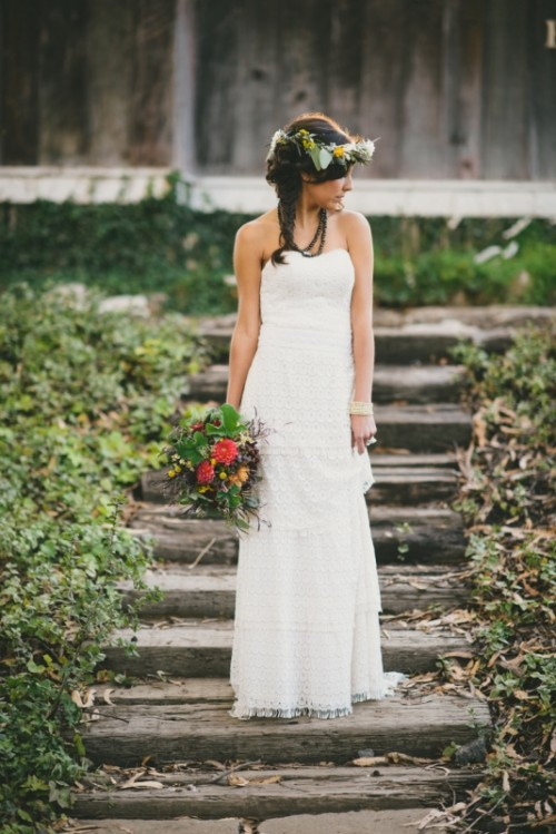 a strapless boho lace sheath wedding dress with a layered skirt and a floral crown for a chic look