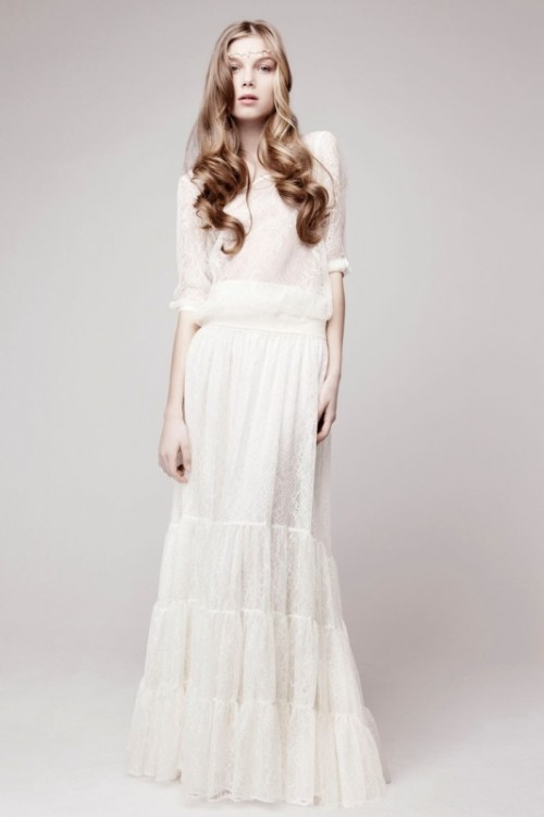 a baggy lace wedding dress with short sleeves, a draped waistline and a tiered skirt