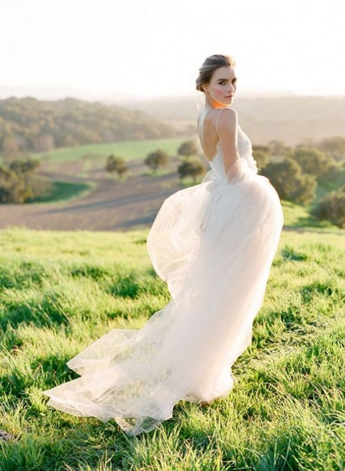 a romantic wedding dress with a lace bodice on spaghetti straps and an open back and a flowy skirt
