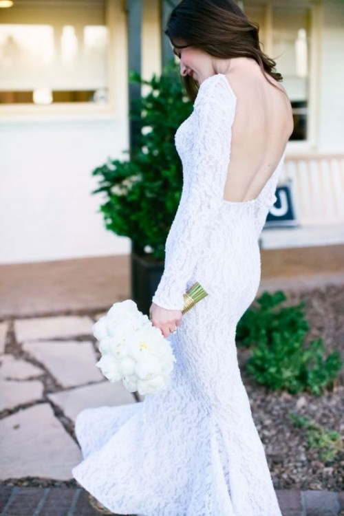 a white lace sheath wedding dress with an open back and long sleeves is a stylish idea