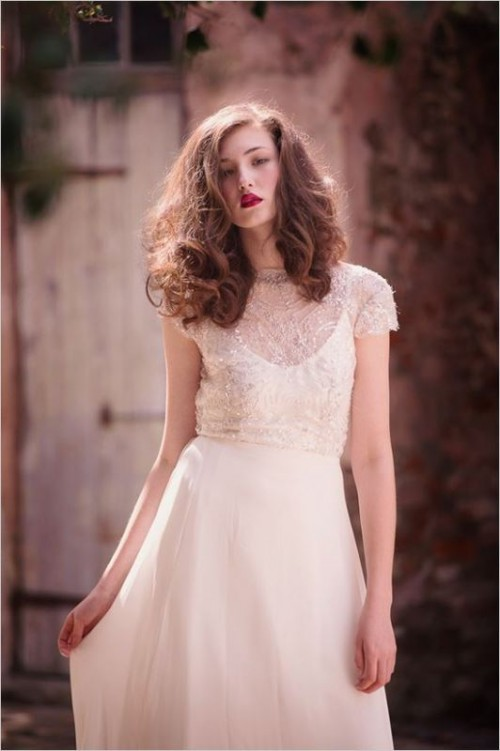 a chic modern bridal combo of a white plain wedding dress on straps and a sheer embellished cropped top