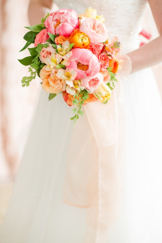 a colorful summer wedding bouquet made of pink and blush peonies, orange and yellow blooms and greenery is fun and bold