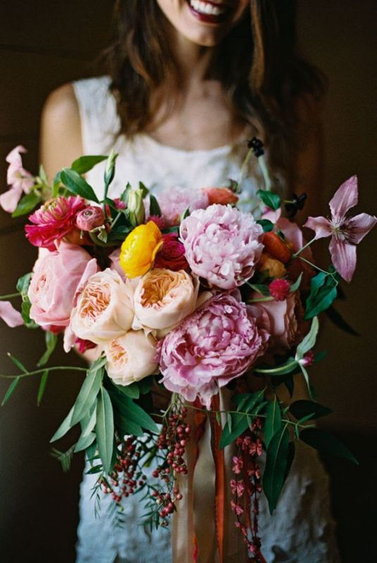 a beautiful and bold wedding bouquet of pink, coral and peachy peonies, greenery and berries plus ranunculus is a bold idea for a summer wedding