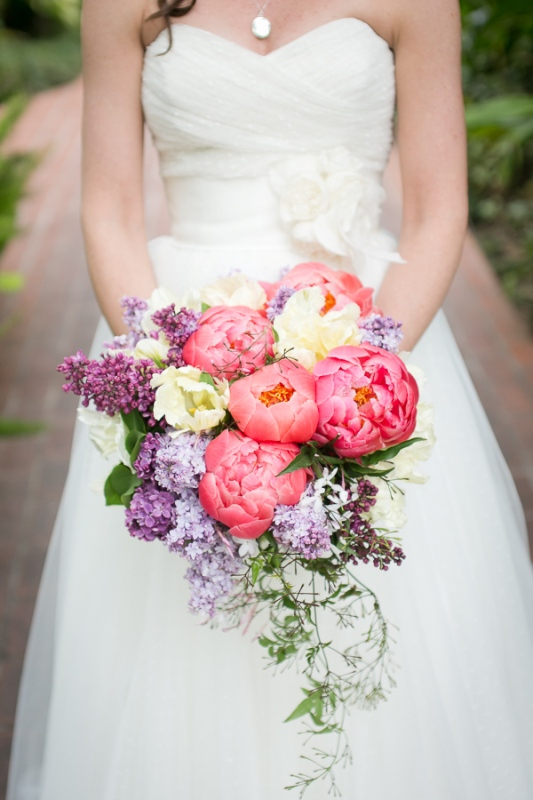 a bold wedding bouquet with coral and white peonies and lilac is a beautiful solution for a bright spring wedding