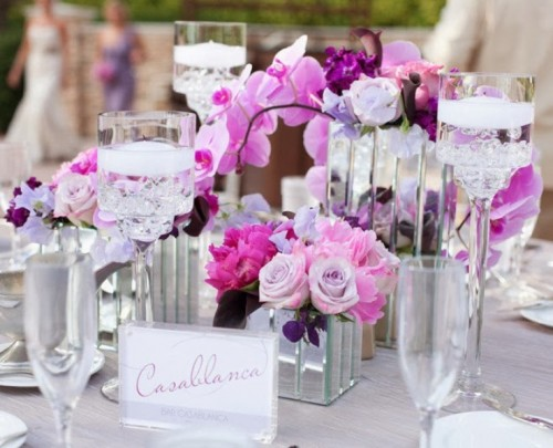 a bright radiant orchid and pink wedding centerpiece with candles and mirror vases is amazing