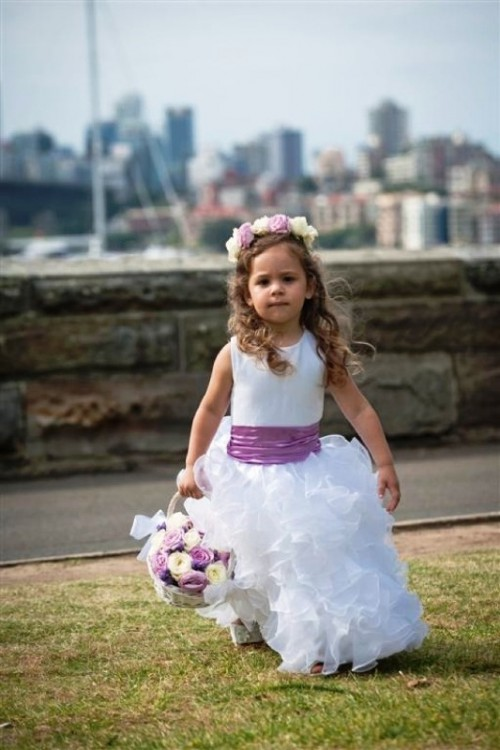 a flower girl wearing a sleeveless white maxi dress with a radiant orchid sash and a matching floral crown plus a basket with blooms