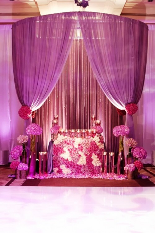 a radiant orchid wedding altar with blooms, candles, radiant orchid curtains and blooms plus lights