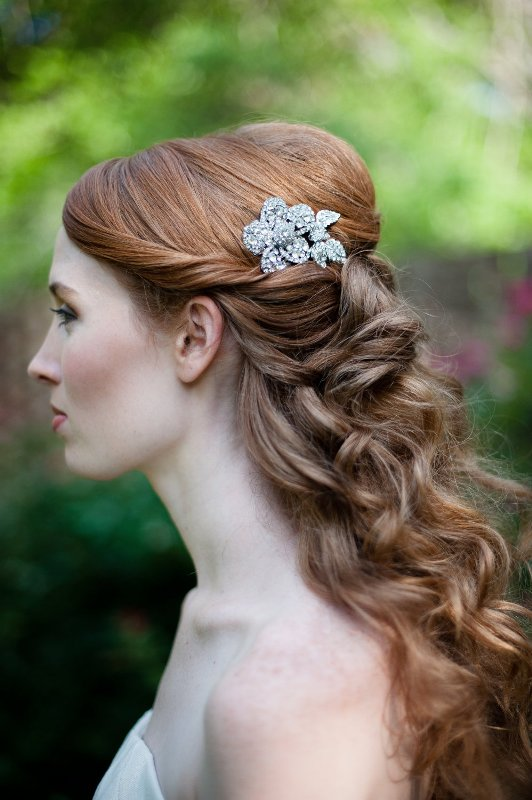 a vintage half updo with waves and curls, twists on top and a shiny rhinetone hairpiece