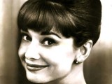 a classic Audrey Hepburn hairstyle – an updo with a volume on top and a fringe, all sleek and elegant