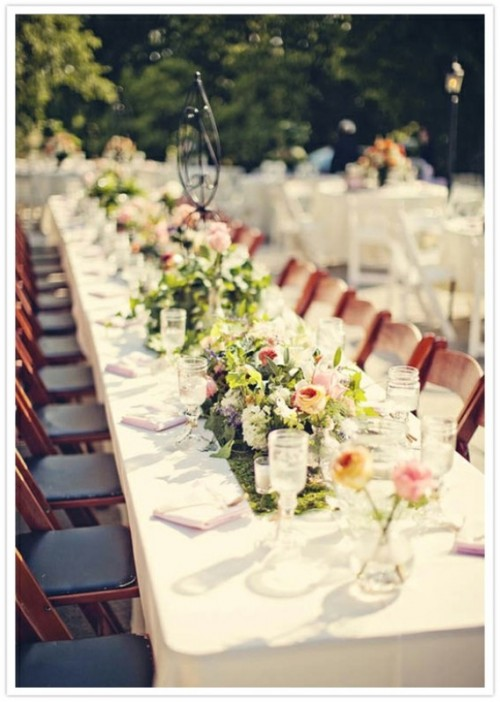 a neutral table setting with a moss runner, colorful floral centerpieces to spruce up long tables