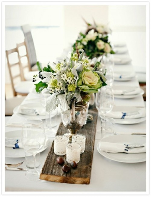 a wooden plank runner with centerpieces, candles and even nuts is a creative idea for a long table