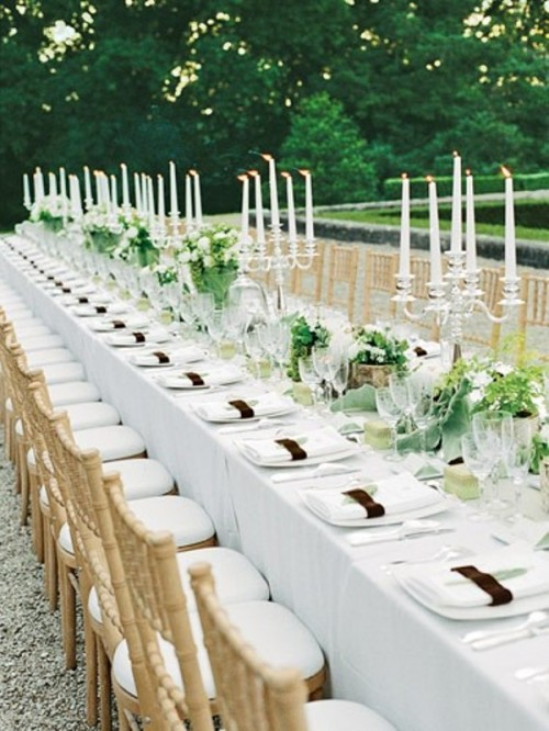 lush greenery and white bloom centerpieces and tall thin candles highlight the length of the tables