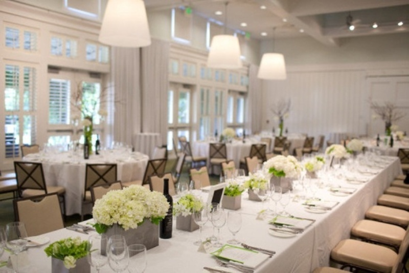 a neutral tablescape with white blooms and greneery, with glasses and green menus