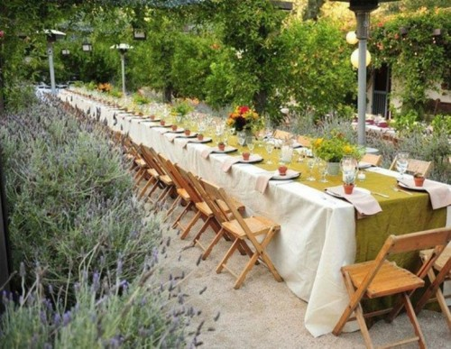 a wide mustard table runner contrasts the neutral tablecloth and bright bloom centerpieces add color