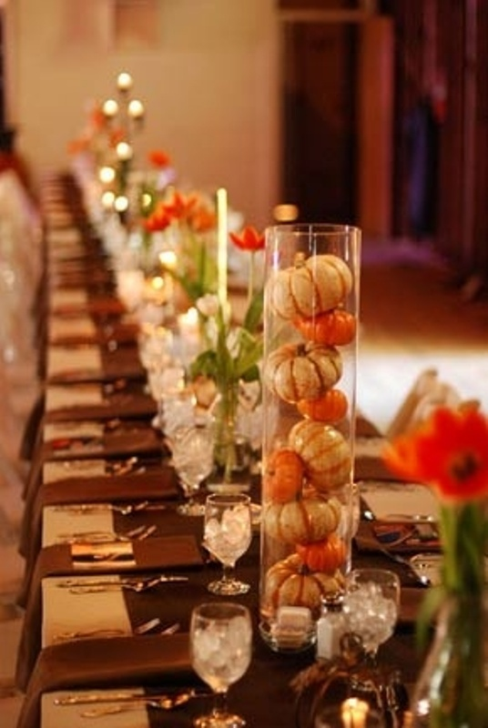 colorful bloom centerpieces and tall clear vases with pumpkins plus candles make the tables look even longer