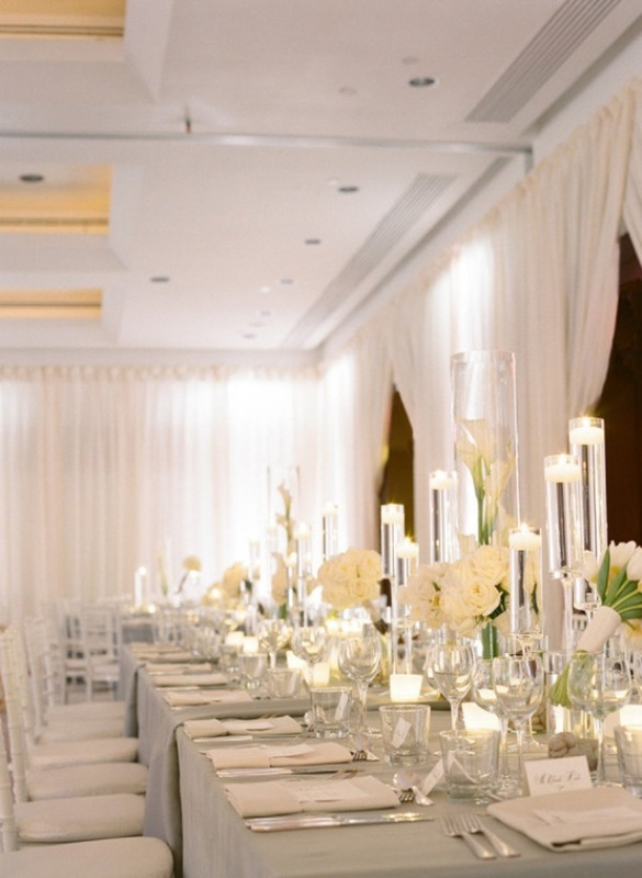 a pure white and ivory formal table setting with candles, floating and usual ones and blooms