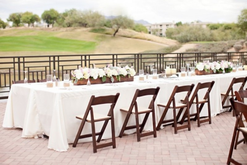 dark stained chairs and plywood planters contrast the white blooms and tablecloths