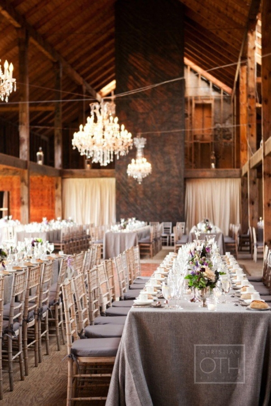 a grey tablecloth and colorful bloom centerpieces plus grey cushions on the chairs