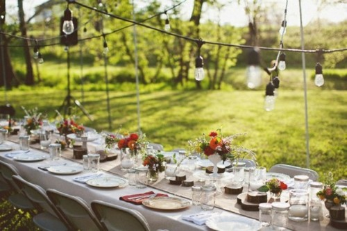 a white tablecloth, a burlap runner, wood slices and white candles plus colorful floral centerpieces