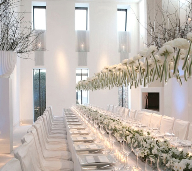 white bloom centerpieces and an overhead decoration visually elongate the tables evne more