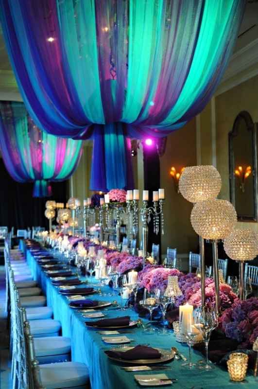 purple floral centerpieces and a turquoise tablecloth are combined with curtain lamps of the same colors