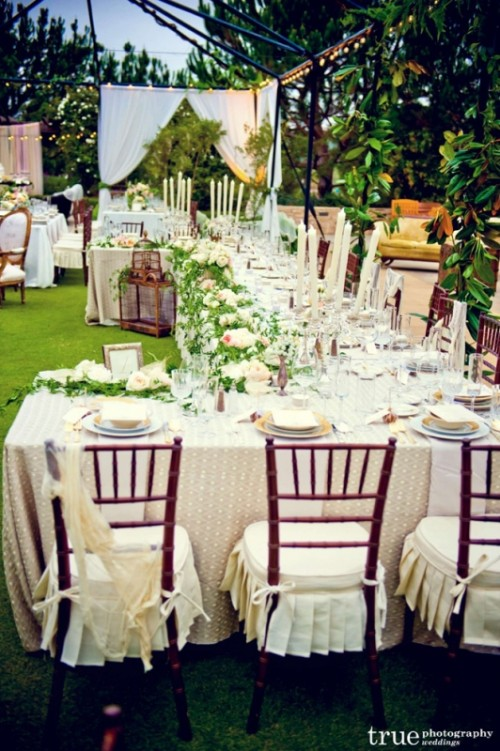 neutral tablescapes with greenery and blush blooms plus candles