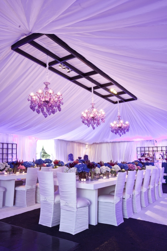 wedding tablescapes with lush purple, burgundy and pink blooms and pink chandeliers