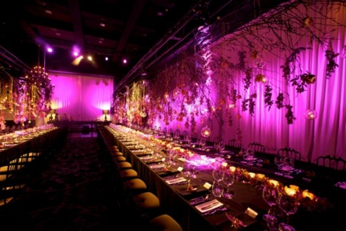 candles and purple blooms match the purple backdrop in the reception space