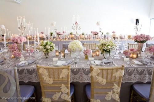 a grey lace tblecloth and neutral lace chair covers plus lush floral centerpieces