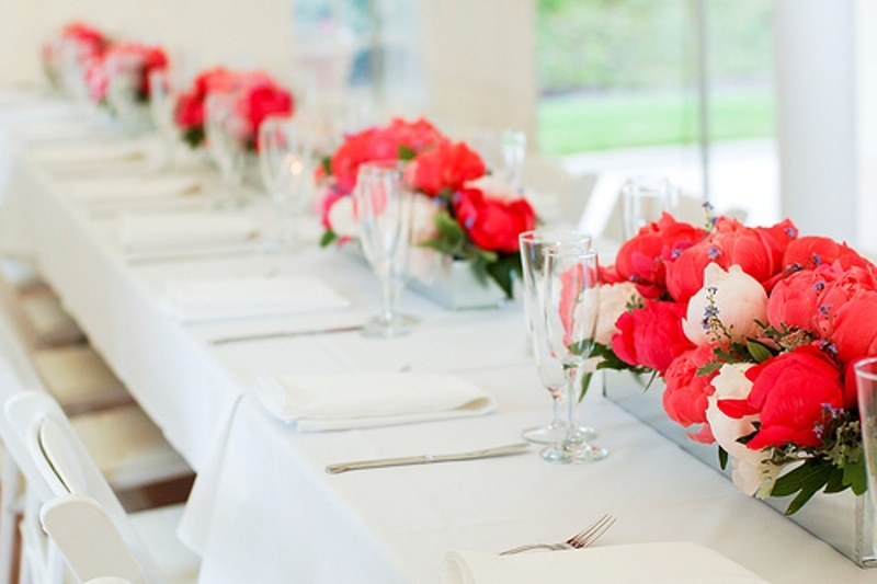 long colorful floral centerpieces contrast the neutral tables