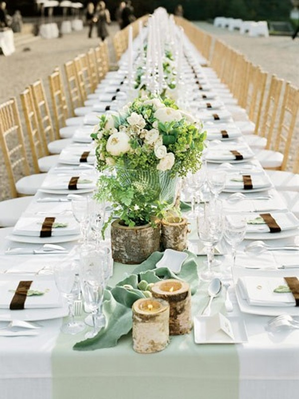 a white tablecloth, a light green table runner, branch candle holders refresh the tablescape
