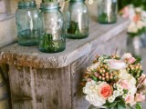 a wooden bench with lush floral centerpieces in pink and white and in blue jars