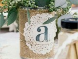 a rustic rehearsal dinner centerpiece of a tin can wrapped with burlap, a doily and baby's breath