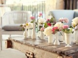 a rustic pallet coffee table with colorful blooms in white vases