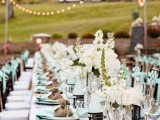 a rustic tablescape done in mint and burlap, with white blooms and candles