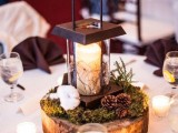 a wood slice with moss, pincones, cotton and a modern metal candle lantern