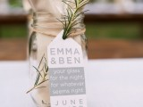 a jar with a napkin and cutlery plus a tag and some greenery for a rustic rehearsal