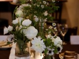 a lush white floral centerpiece in jars decorated with burlap and lace