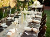 a rustic tablescape with white and yellow blooms and a burlap runner