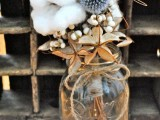 a rustic centerpiece with thistles, cottons, berries for a winter celebration