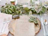 a cozy and chic rustic setting with a wood slice, a greenery runner and some pebbles