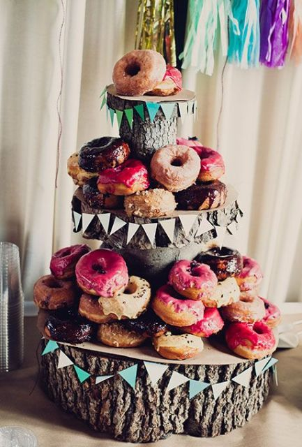 a simple rustic wedding dessert stand of wood slices and tree stumps, with colorful paper banners and lots of sweets