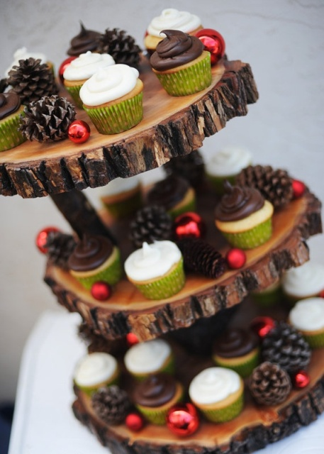 a cool woodland wedding sweets stand of wood slices, with pinecones and mini red Christmas ornaments is ideal for a rustic holiday wedding