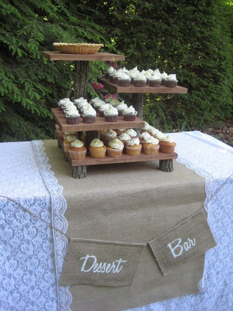 a wooden dessert stand of wooden planks and tree branches is a lovely idea for a rustic or a woodland wedding