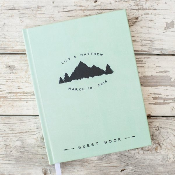 a green wedding guest book with mountains printed will remind your of the place where you tied the knot