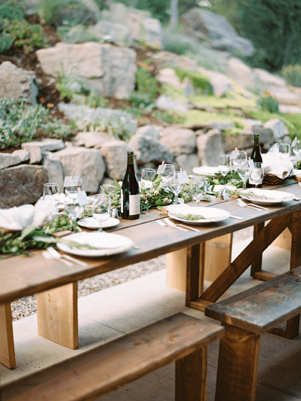 a neutral and nautral tablescape with greenery and uncovered wooden tables and benches for a mountain wedding