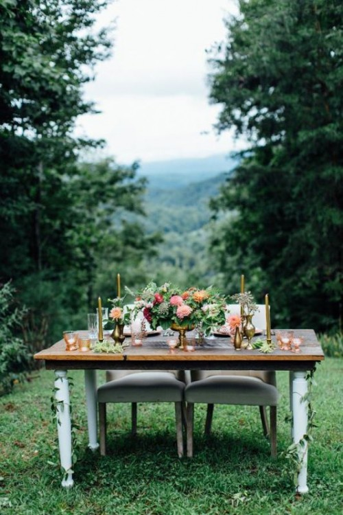 a sweetheart table decorated with greenery and blooms and placed right in the mountains